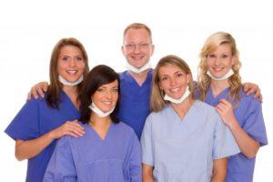 smiling dental team in blue scrubs